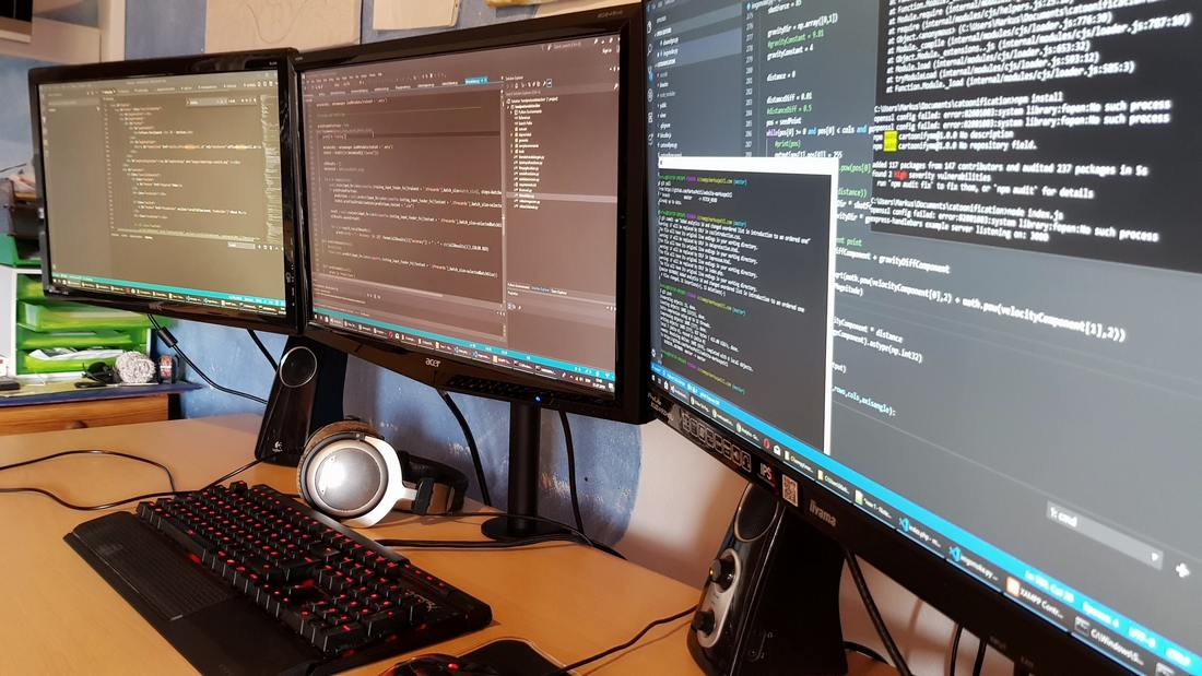 3 computer monitors showing code also a keyboard and heaphones on a desk